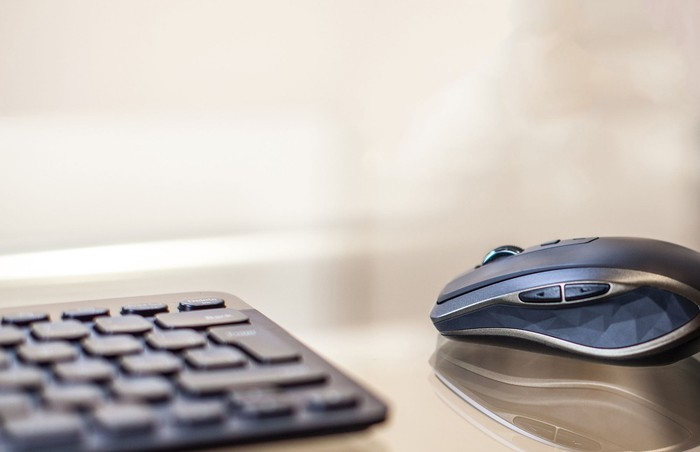 Logitech's MX Anywhere wireless mouse next to a keyboard.