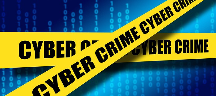 Cyber Crime yellow tape over blue digits background.