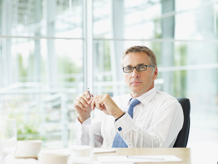 A business man wearing glasses sits behind his desk in front of a glass wall.