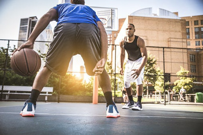 Two young men playing basketball outside