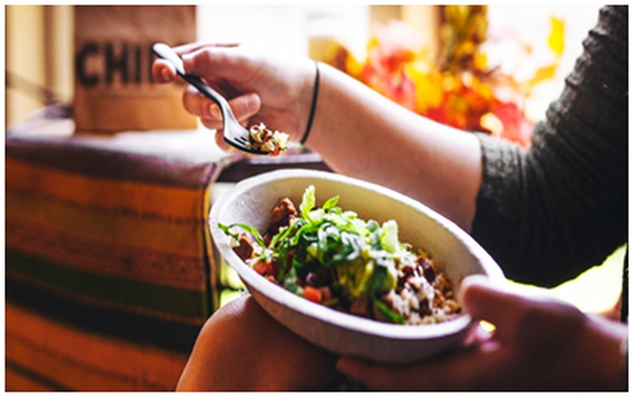 A woman holds a Chipotle burrito bowl on her knee with one hand, and a fork in the other.
