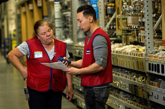 Two Lowe's employees discussing their tasks with each other.