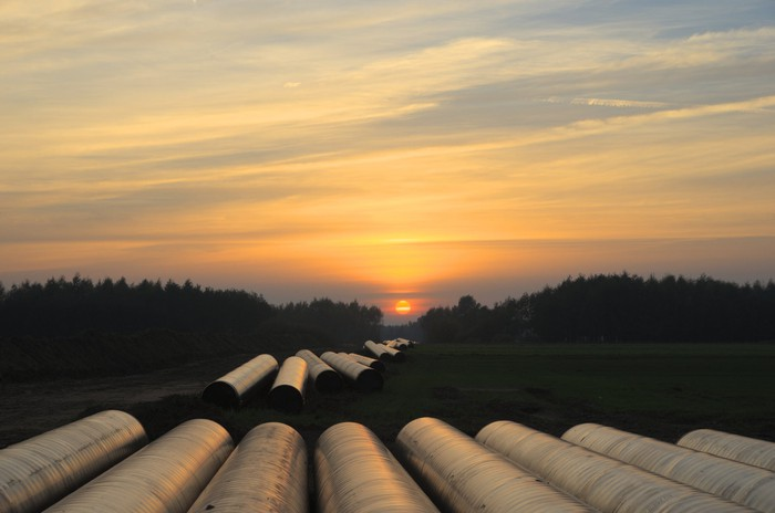 Pipeline segments laid out for construction, against the backdrop of a setting sun.