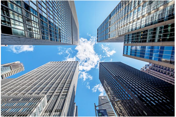 An upward-looking view of a cluster of skyscrapers, with a blue sky and puffs of clouds above them.