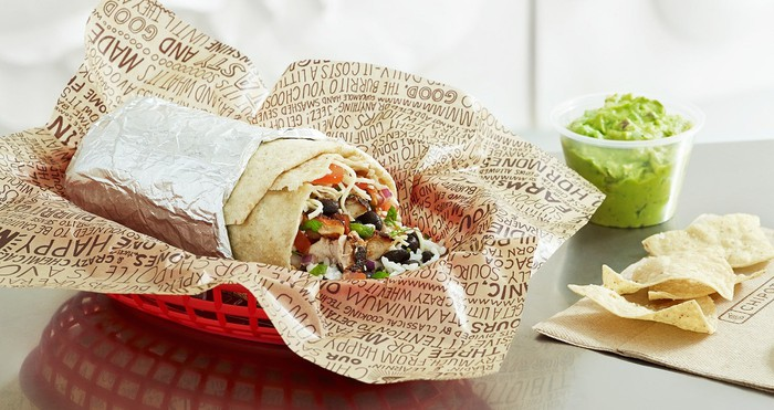 A Chipotle burrito with guacamole and chips.