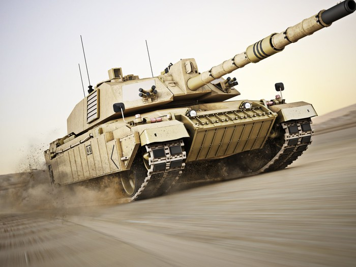 A tank kicks up dust from its tracks.