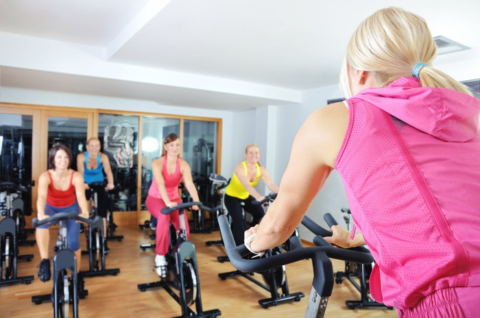 Women at a spinning class on exercise bikes.