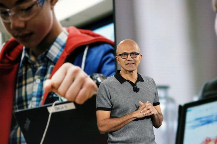 Satya NAdella speaking on a stage with picture of young boy operating a piece of machinery behind him.