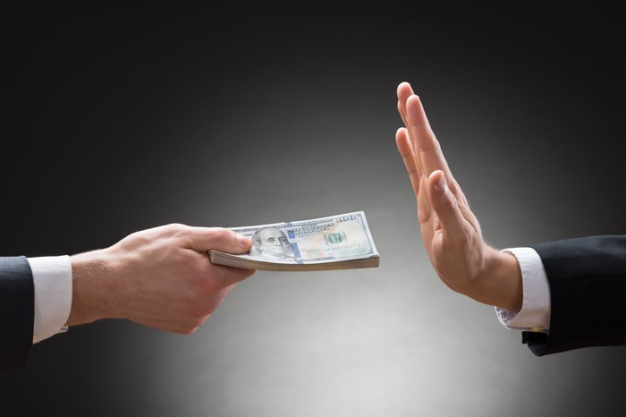 One person refusing cash from another person