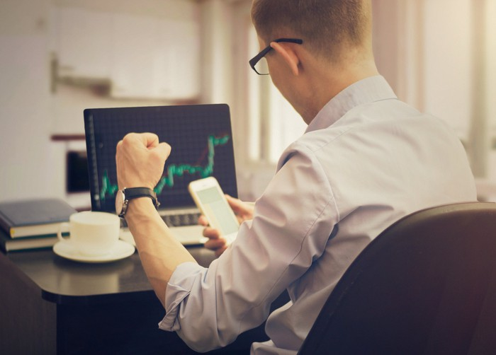 A man watches a stock rally on his PC and smartphone screens.