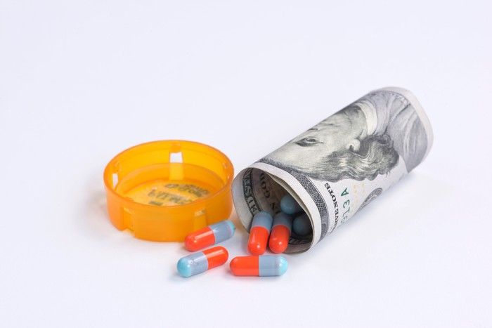 Hundred dollar bill in the shape of a pill container will pills coming out of top.