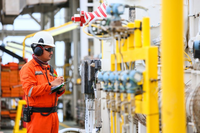 A man in an orange suit and a white hard hat holds a notebook and pen as he checks components at an oil and gas processing plant.