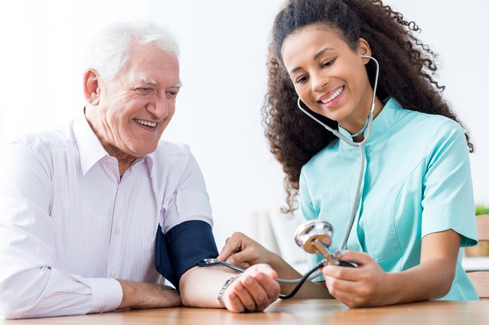 A nurse with a stethoscope checks the blood pressure of a senior who has a cuff on his arm.
