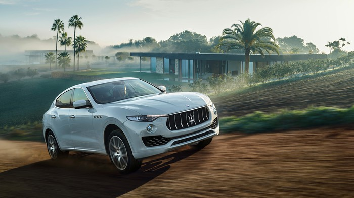 A white Maserati Levante SUV in a tropical setting.