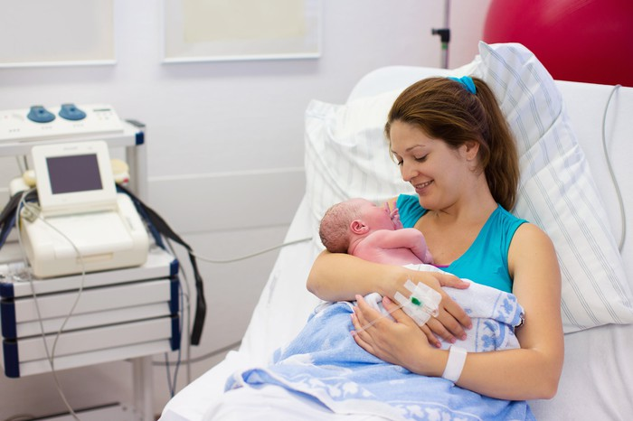 Mom holding newborn as she is seated in hospital bed