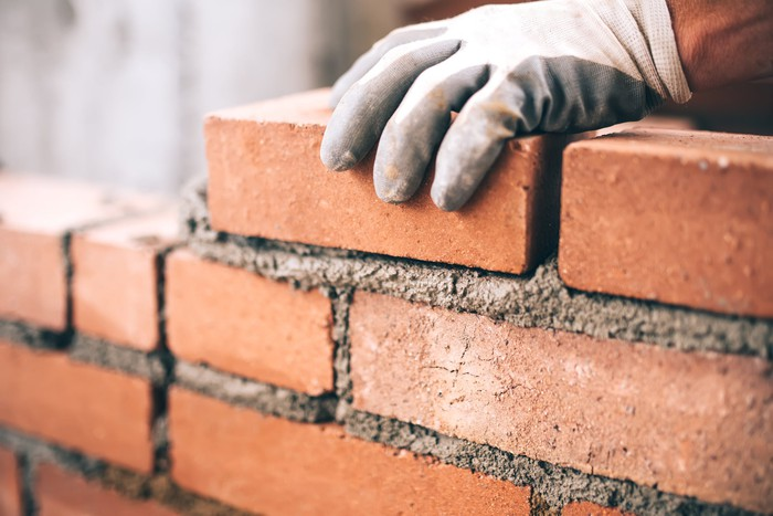 A bricklayer installing bricks on a construction site.
