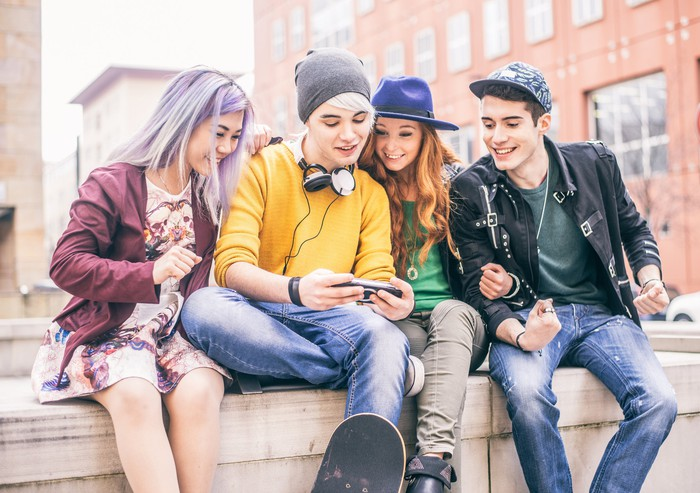 Young people gathered around a friend using a cellphone.
