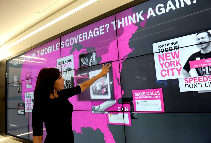 A woman points to a board in a T-Mobile store.