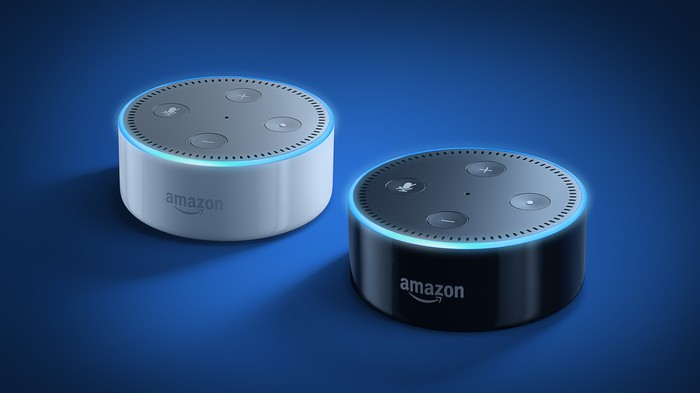 Two Amazon Echo Dot devices, one white and one black, on a blue mat