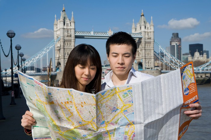 Two tourists at Tower Bridge look at an unfolded paper map.