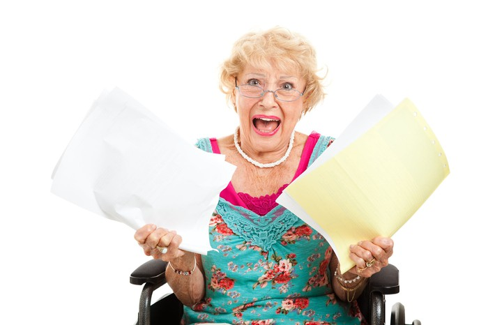 older woman with papers in each hand, looking apalled