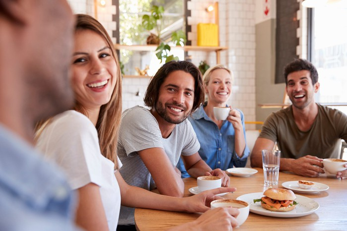 A group of millennials smile as they sit around a table, with food and drink in front of them.