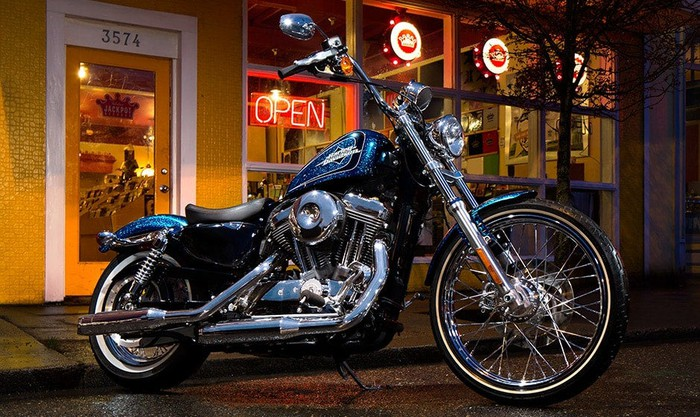 "Harley-Davidson Sportster Seventy Two parked in front of a store with a neon ""Open"" sign in the window"