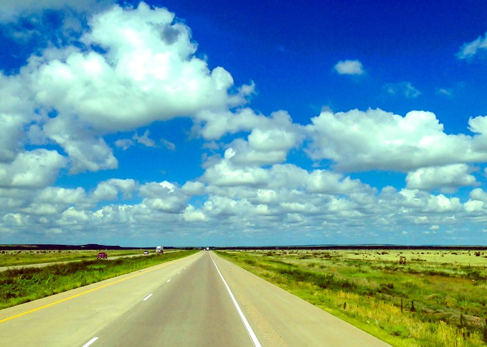 Open-road highway in North Dakota under a blue sky with white puffy clouds