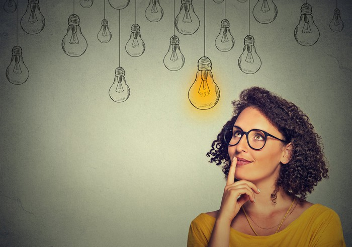 A woman with thoughtful expression looking at hanging light bulbs, one of which is lit.