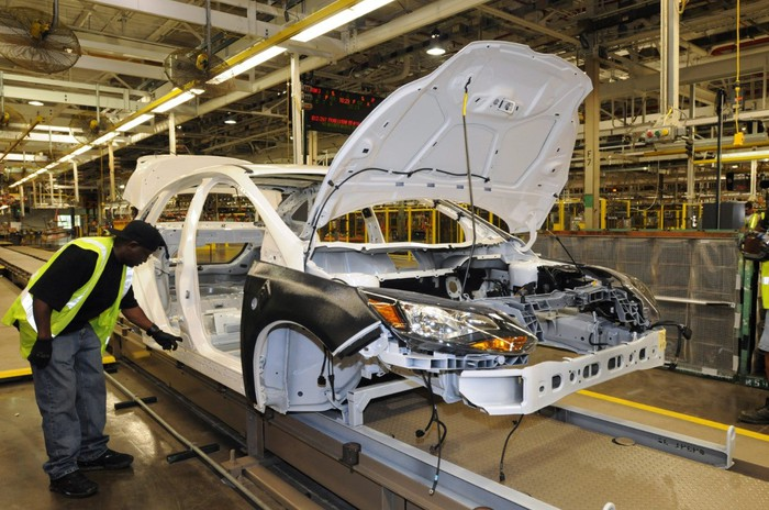 A worker inspects a partially-assembled Ford Focus on the production line at Ford's Michigan Assembly Plant in Wayne, MI.