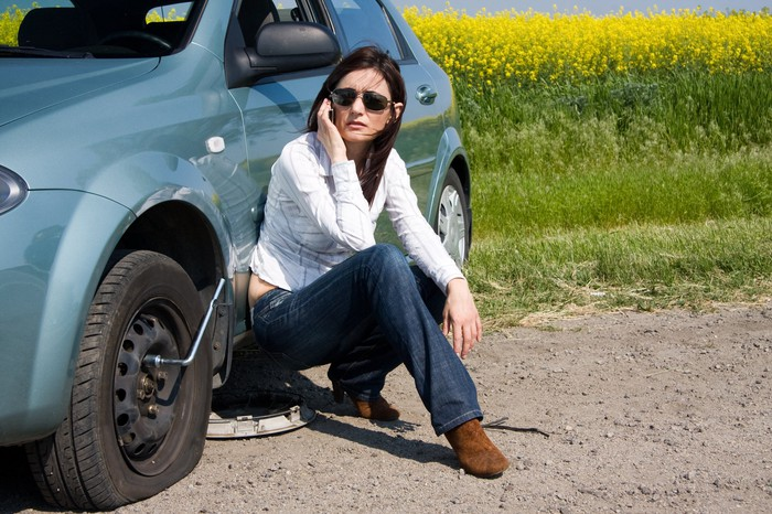 Woman calling on a cell phone next to a flat tire