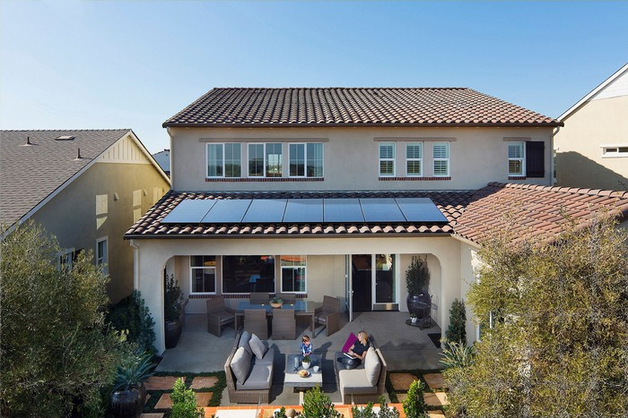 Rooftop solar panels on a Spanish-style home, with a woman and child sitting on a patio sofa outside.
