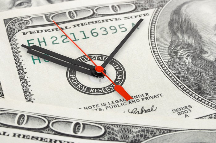The Federal Reserve seal on a hundred-dollar bill is made to resemble a clock, with black hour and minute hands and a red second hand,