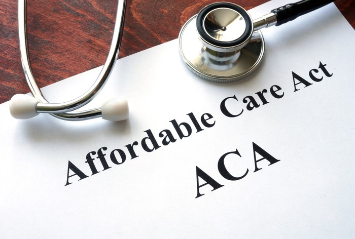 "A piece of paper displaying the words ""Affordable Care Act"" with a stethoscope on top"