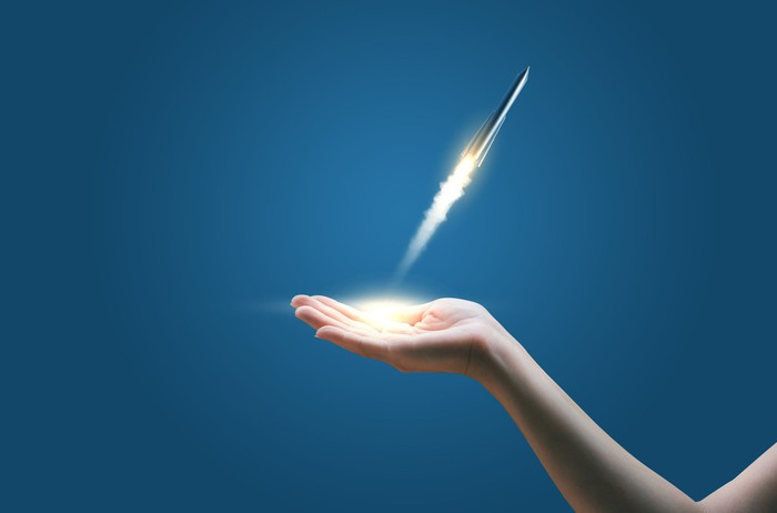 Miniature rocket taking flight from a person's hand.