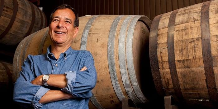 Boston Beer founder Jim Koch in front of beer barrels.