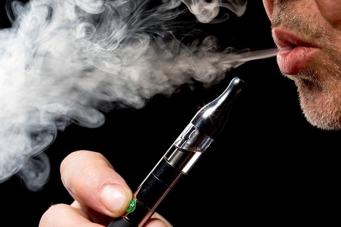 An electronic cigarette user exhaling vapor.