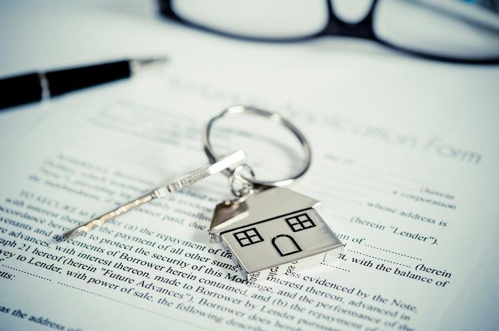 A pen, pair of glasses, and a house key rest on top of a mortgage application.