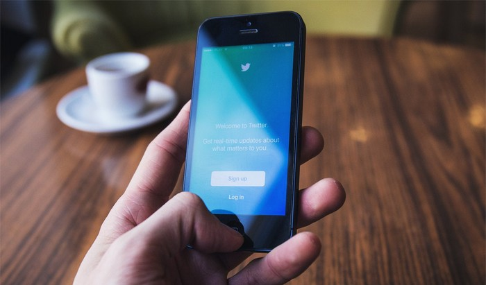 A hand holds a smartphone over a wooden table, with a cup and saucer in the background. On th screen is the Twitter app.