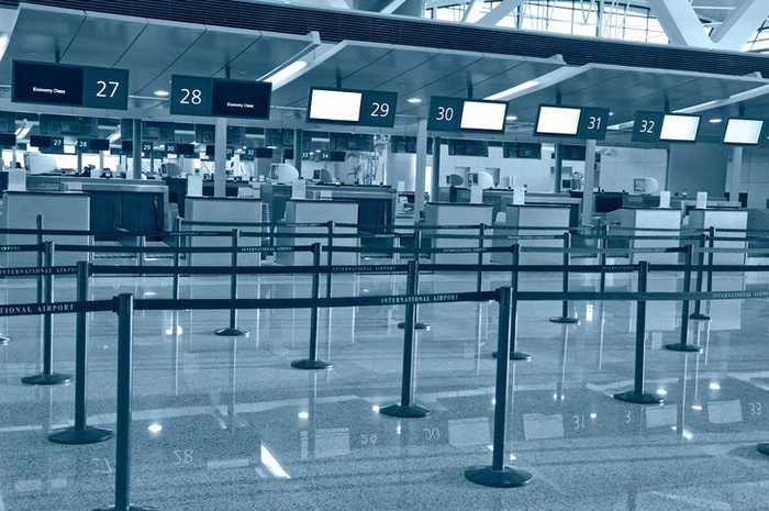 Empty airport ticket counters in greyscale