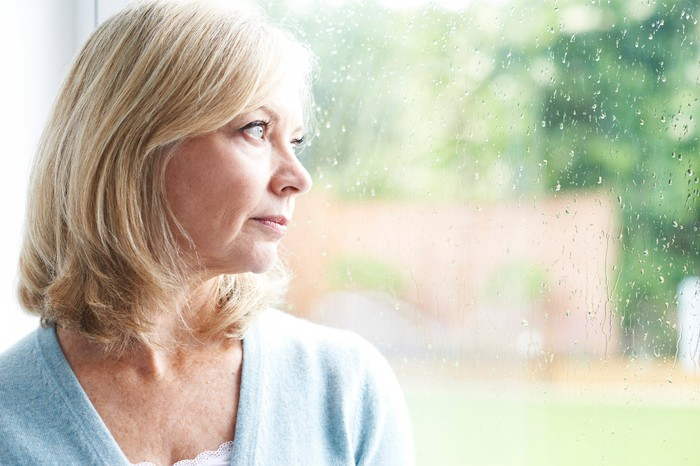 Middle-aged woman looking out the window on a rainy day