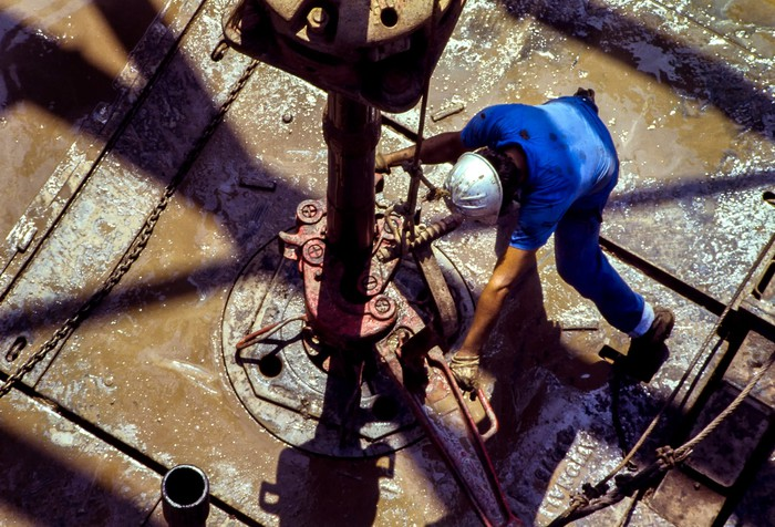 An oil rig worker fitting a pipe