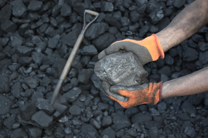 Gloves hands holding large chunk of coal