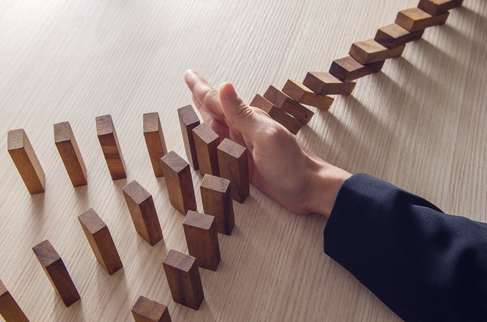 Hand preventing wooden blocks from falling and causing a cascading chain reaction