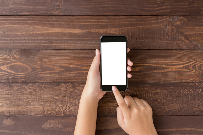 Two hands holding a smartphone with wooden slats in the background.