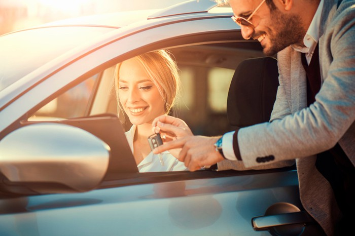 A woman receiving the keys to a rental car