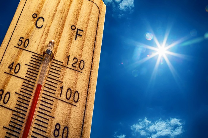 A wooden thermometer in the sun on a hot day.