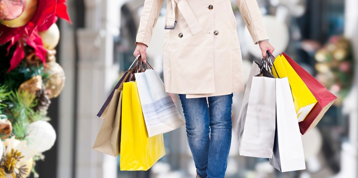 Woman leaving a retail store with shopping bags in her hands.