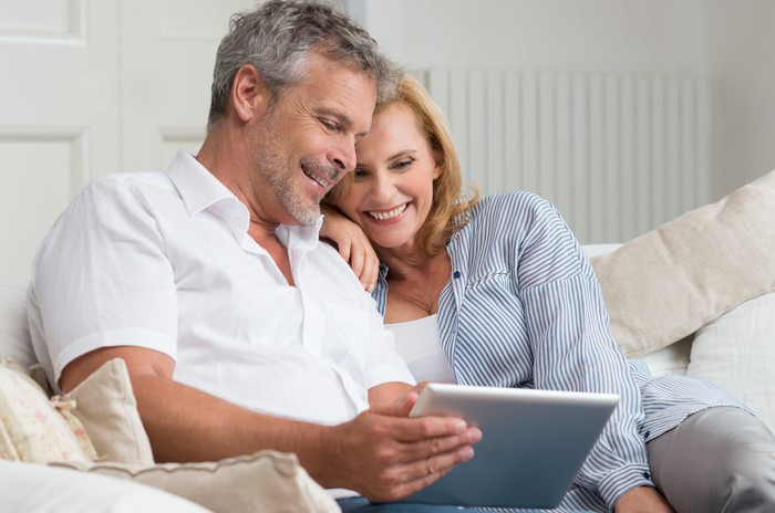 50-something couple looking at a tablet.