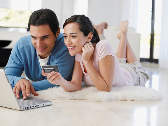 Man and woman lying on floor while types into laptop while woman holds credit card.